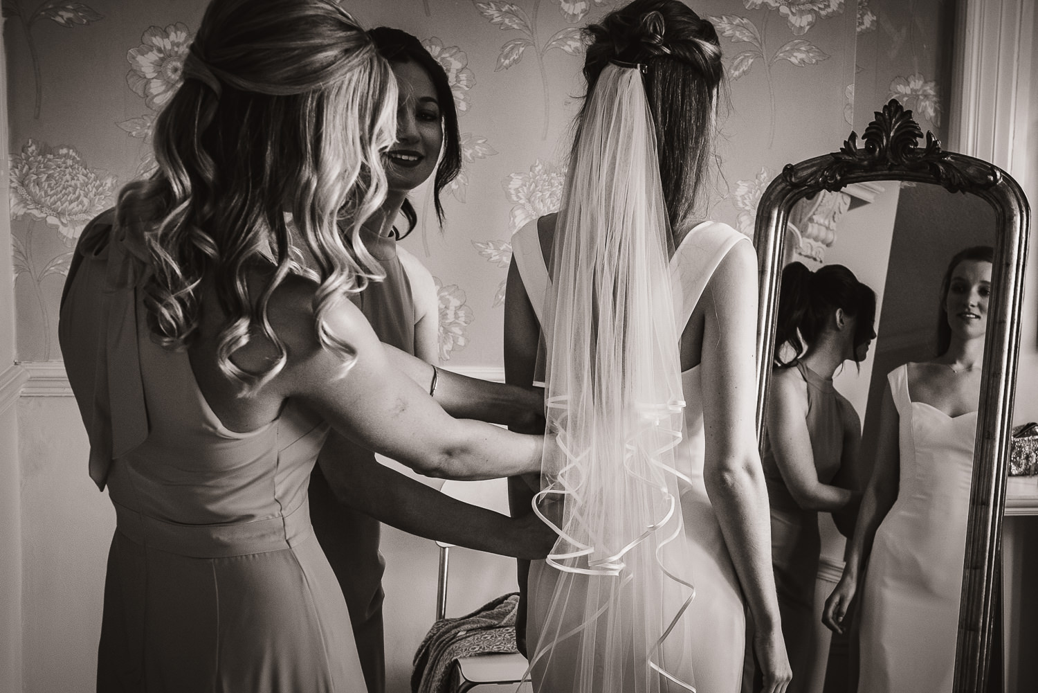 bridesmaids tying the back of the wedding dress