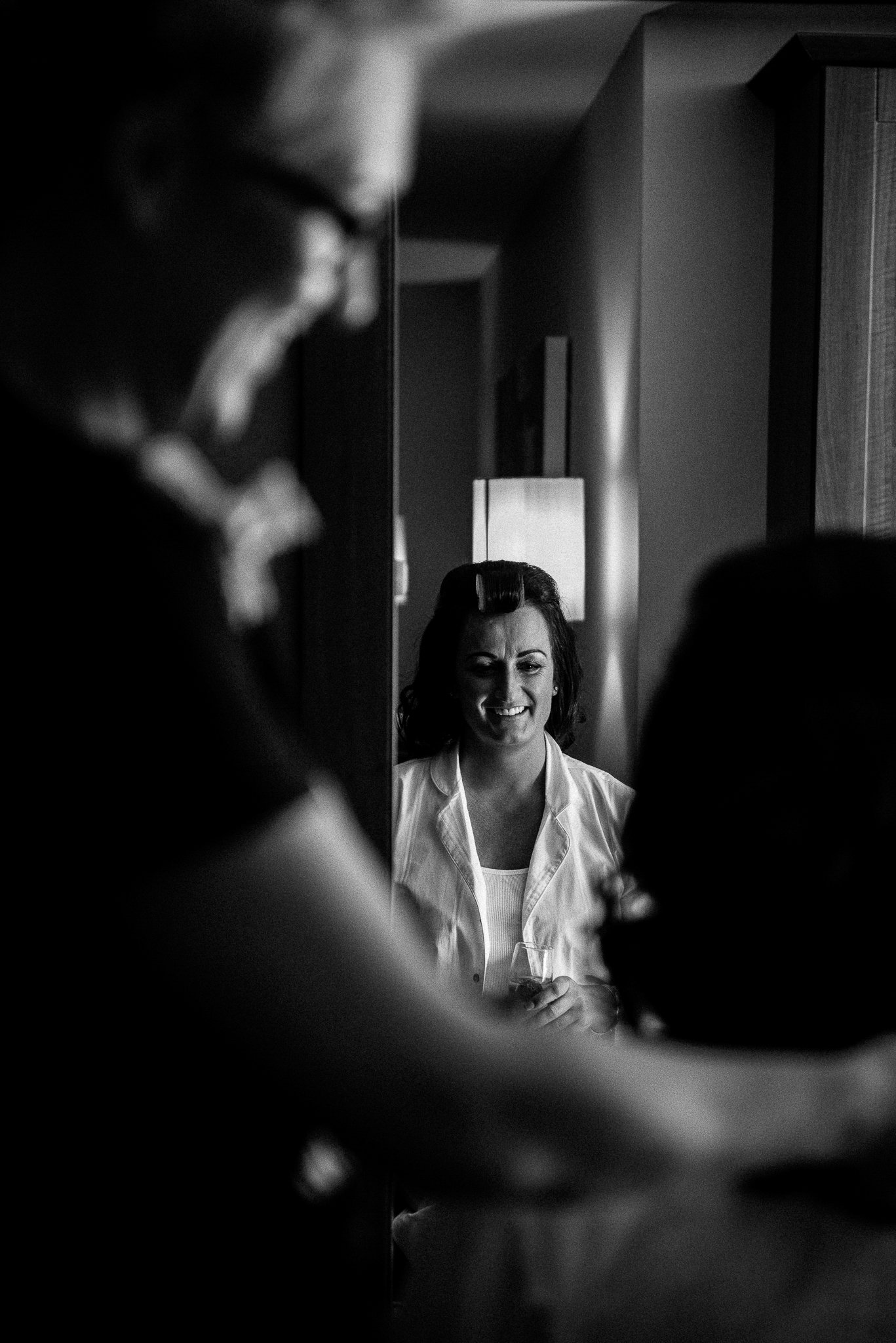 bride having her makeup applied in front of the mirror