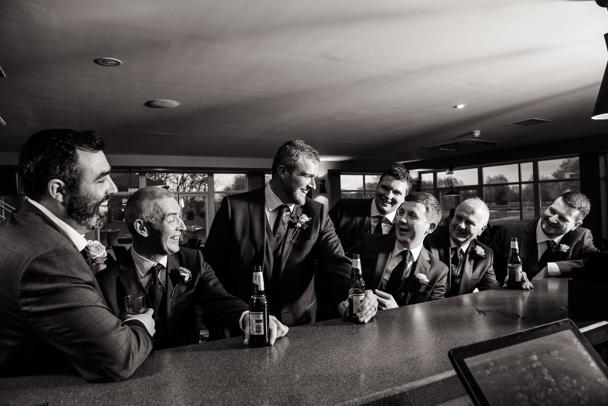 groom and groomsmen having a laugh and a joke at the bar