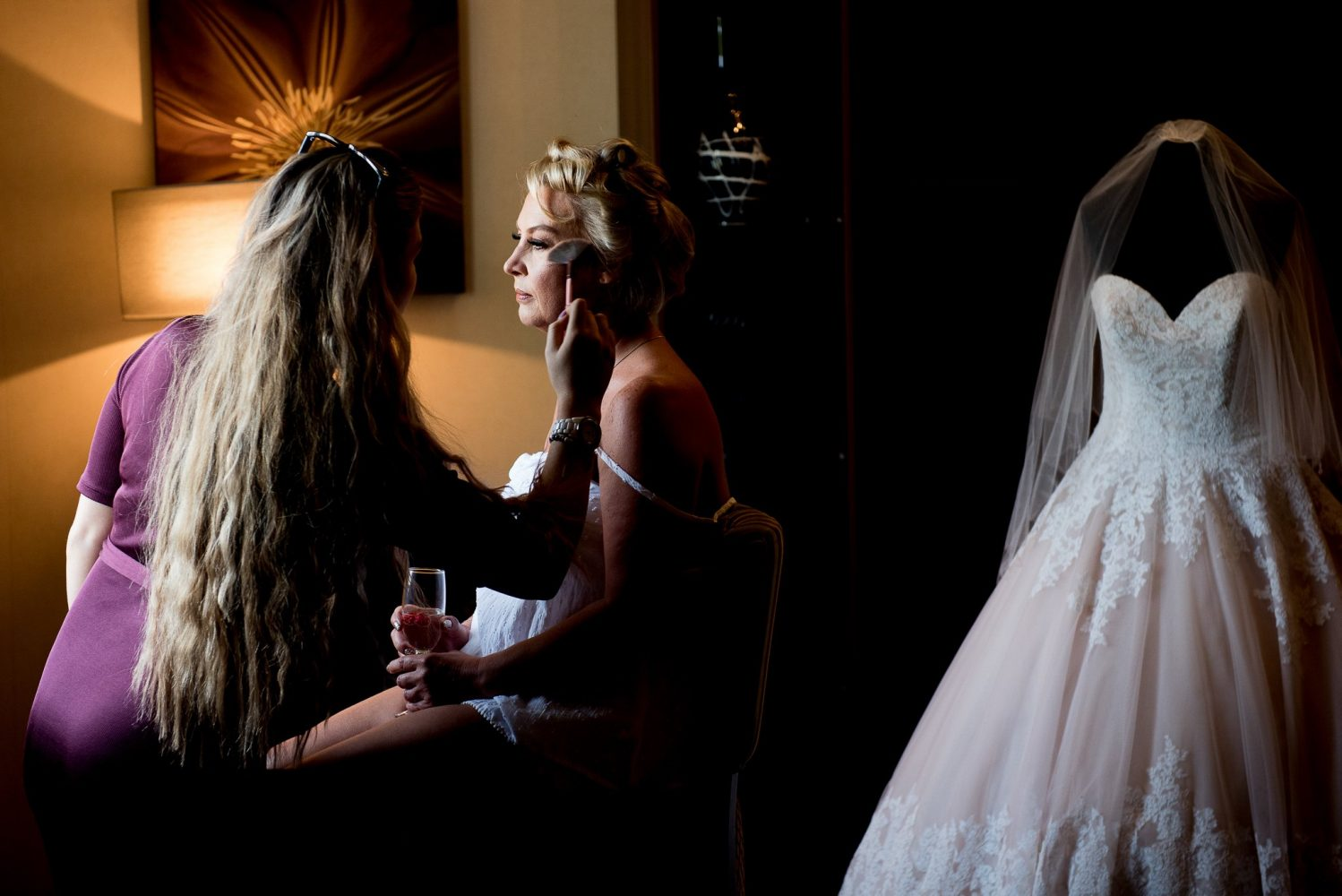 bride having in makeup applied in natural window light by Liverpool Wedding Photographer Gavin Alexander