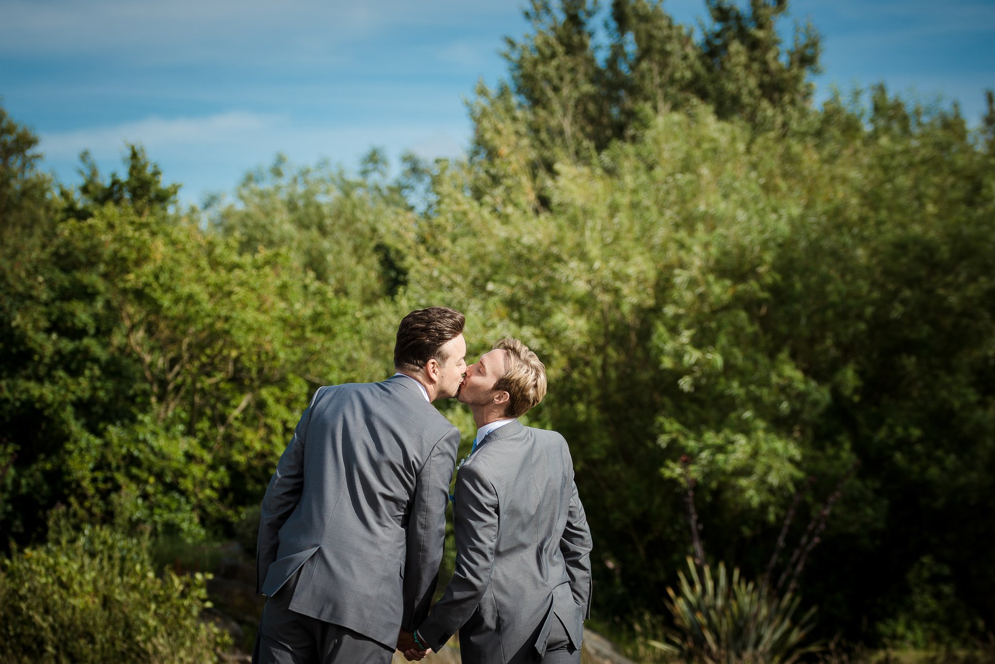 groom and groom holding hands kissing