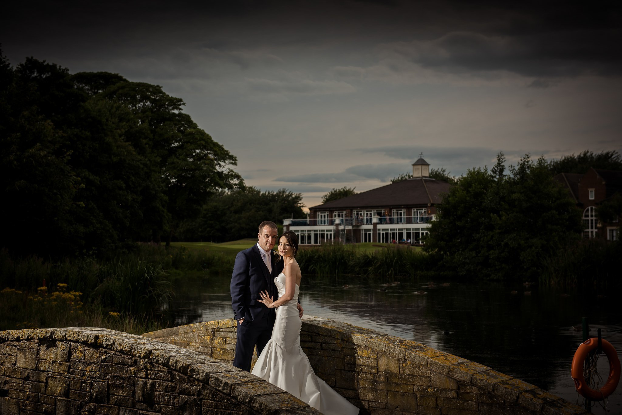 bride and groom standing on a bridge