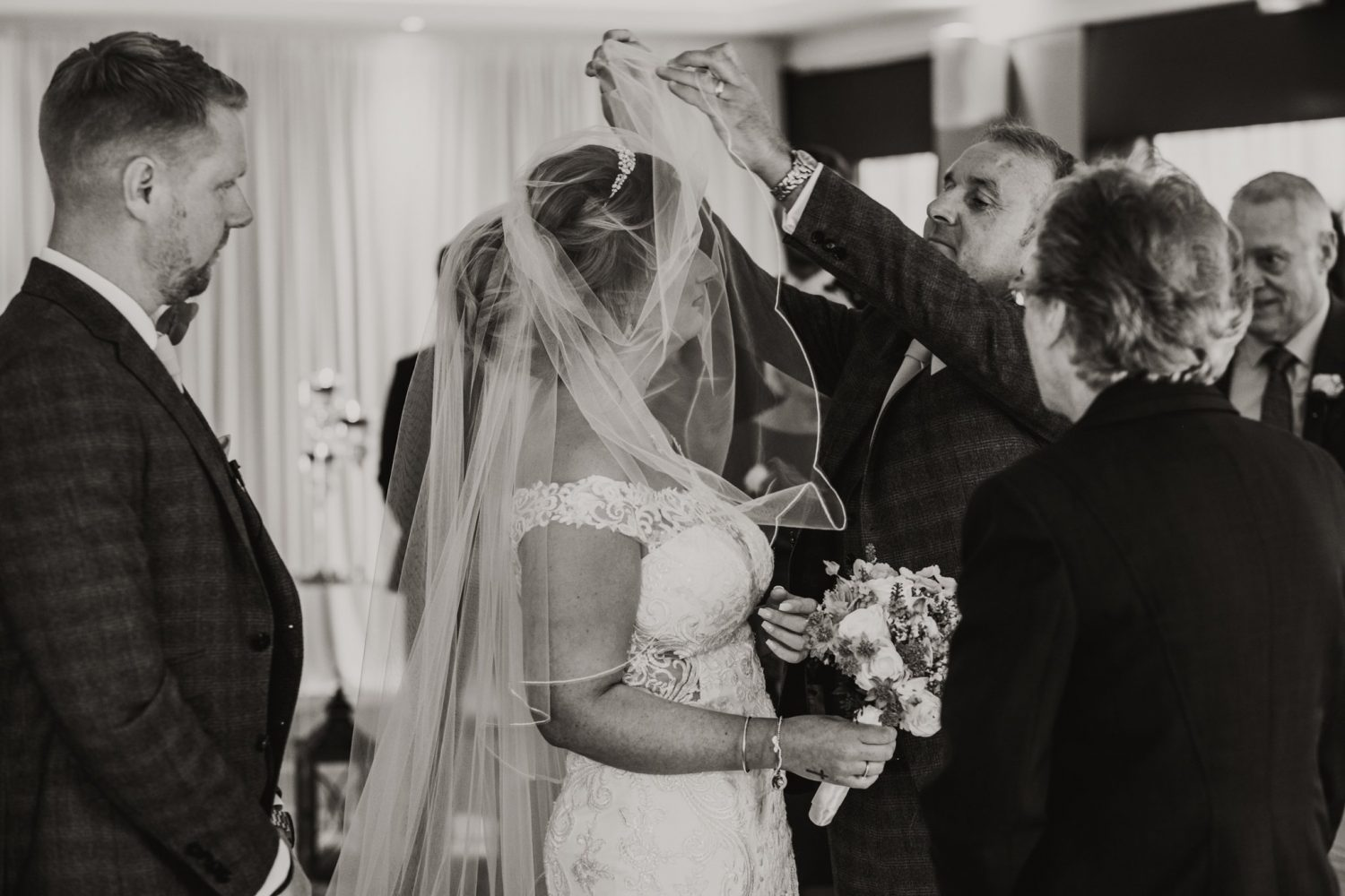 father of the bride lifting the bride's veil