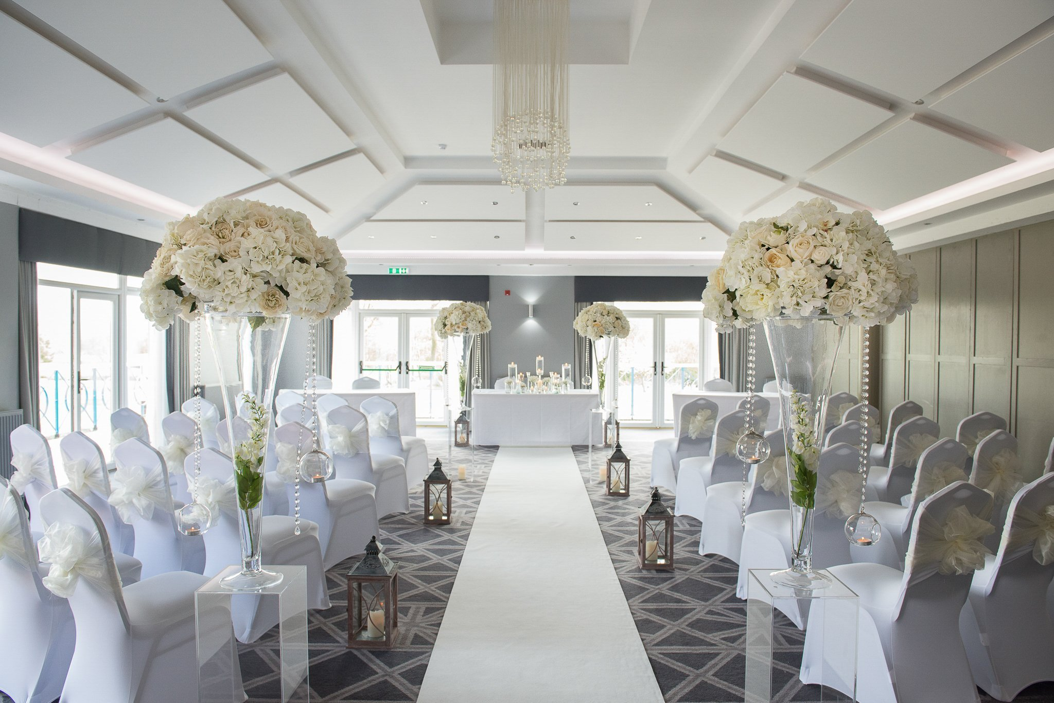 ceremony room venue dressing large flower arrangements with chair covers