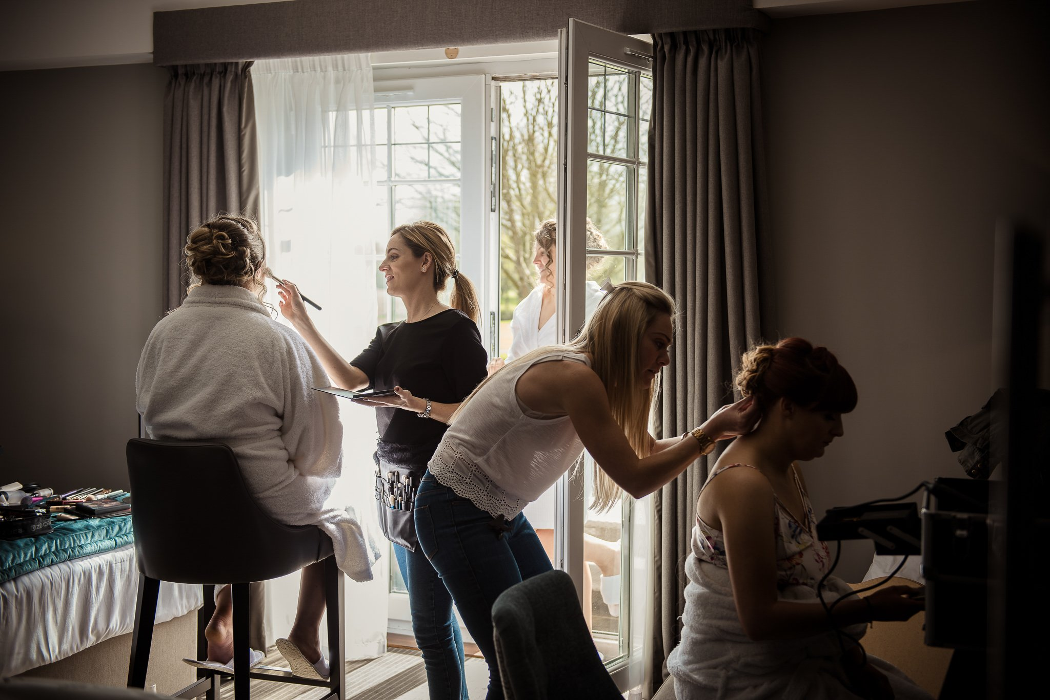 the girls having the hair and makeup done during bridal prep