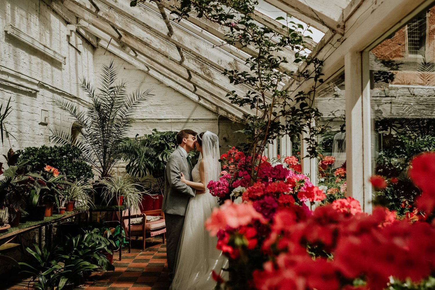 bride and groom in a greenhouse with lush red flowers