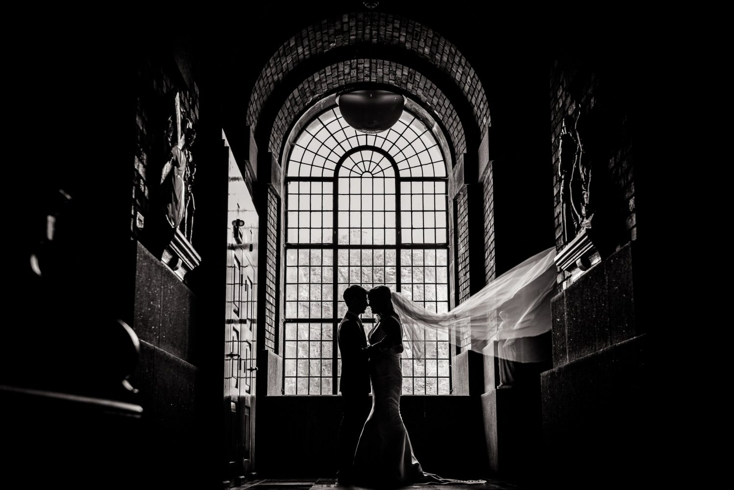 bride and groom silhouette in front of church window