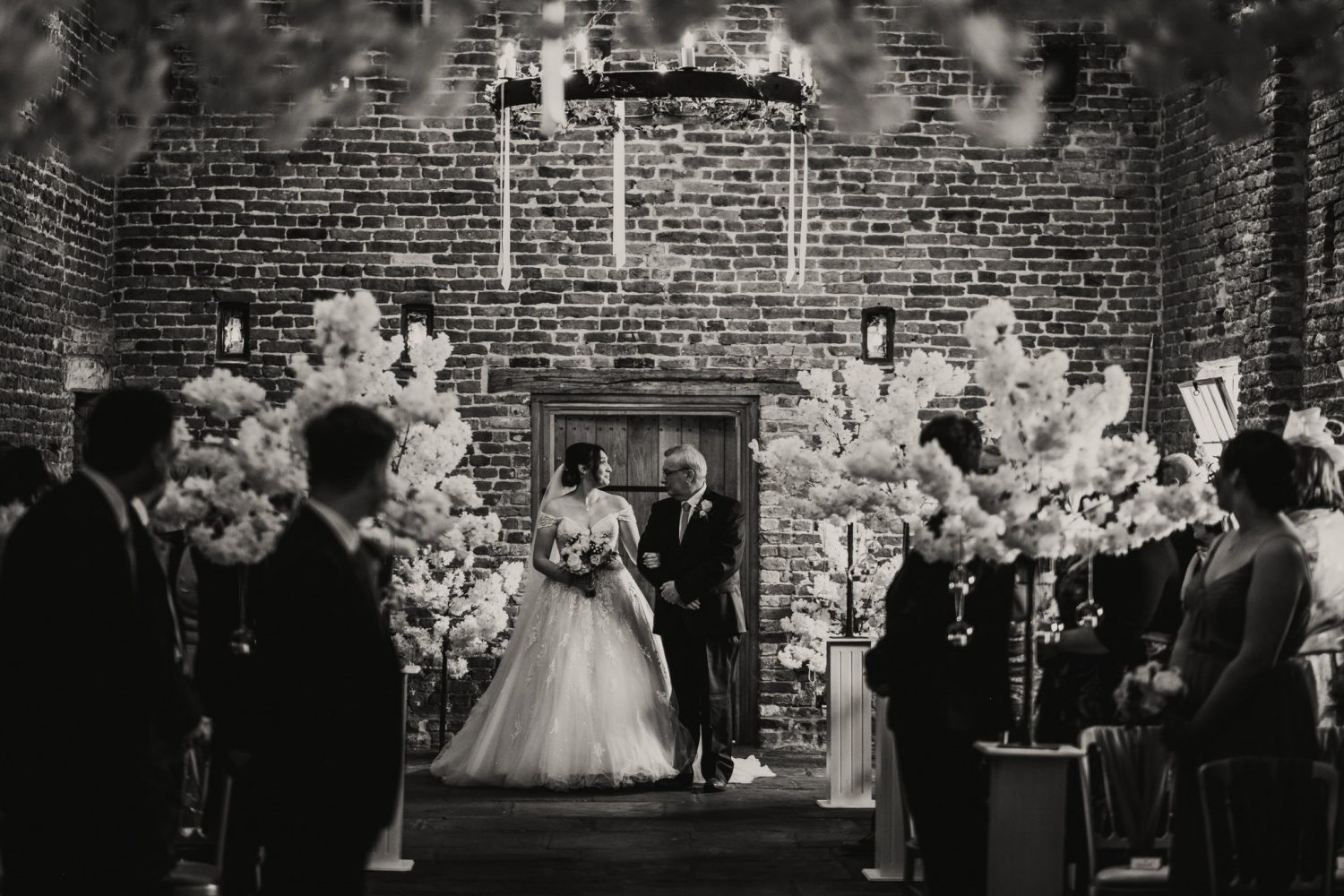 father walking bride down the aisle in black and white