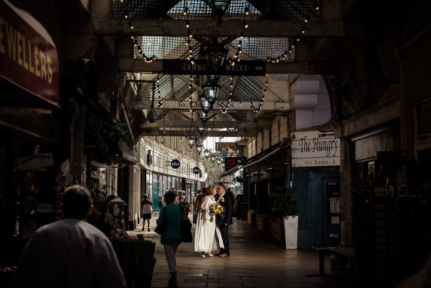 bride and groom portrait in a busy shopping arcade