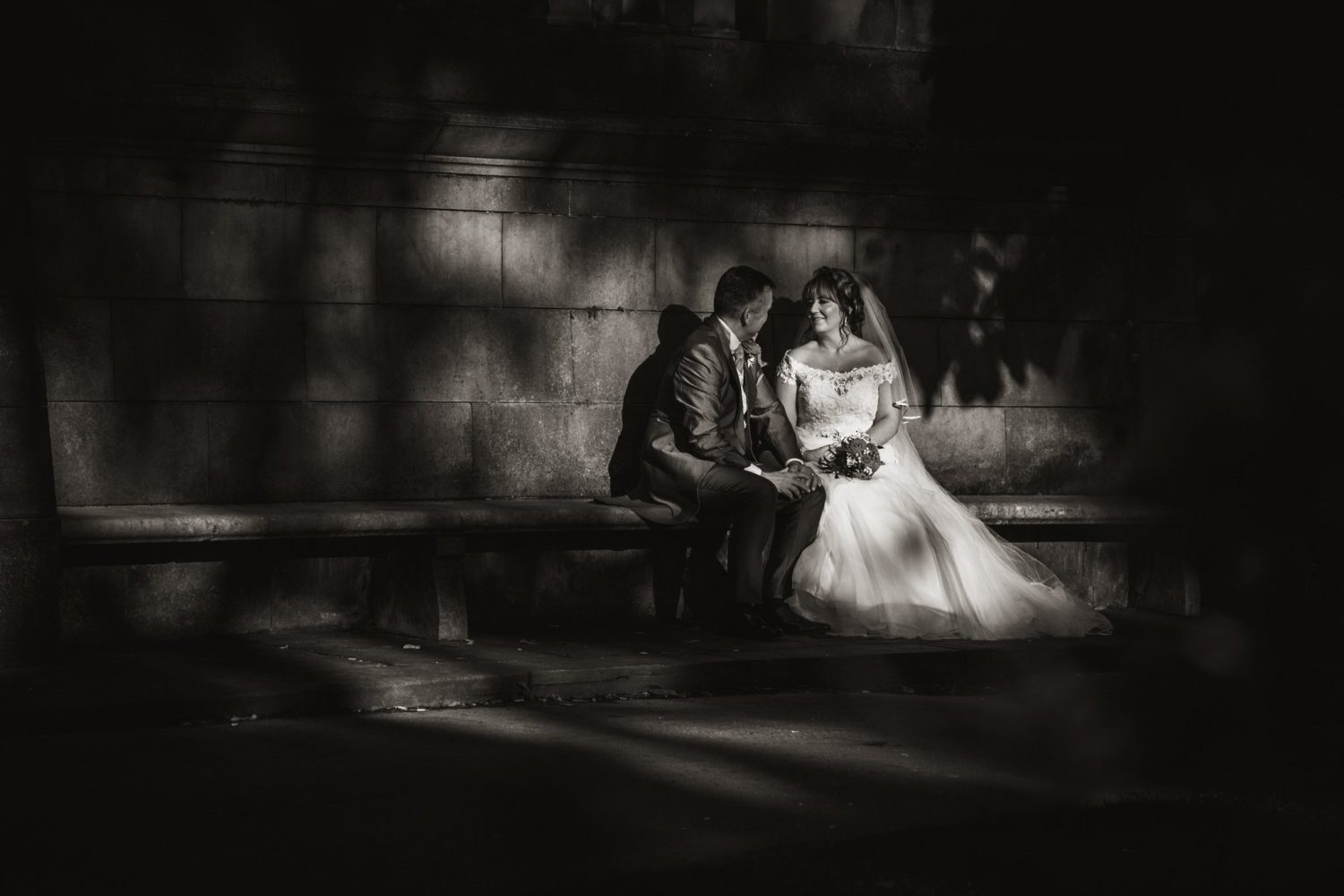 bride and groom sitting on a bench with leaf shade on the wall behind them