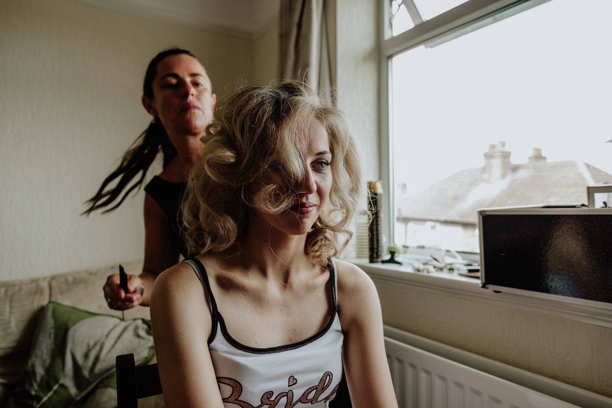 bride having her hair done during bridal preparation captured by Liverpool wedding photographer Gavin Alexander
