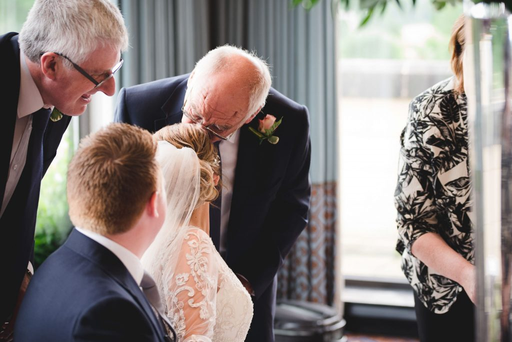 father kissing the bride on the head