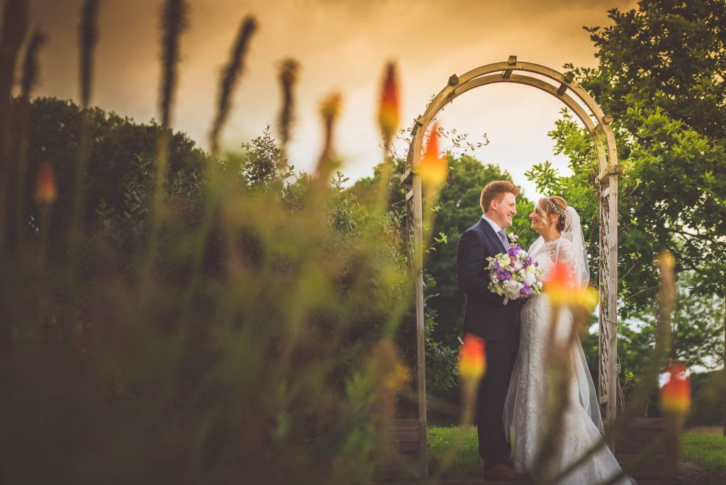 bride and groom posed under a flower arch on the grounds of rooker hall