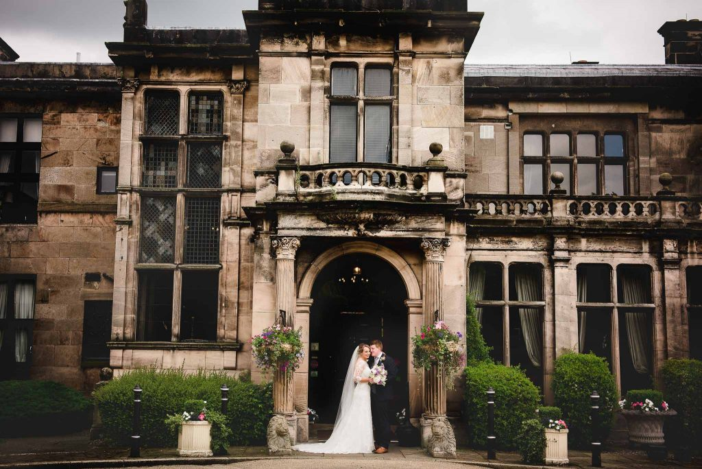 bride and groom posed at the entrance of rookery hall