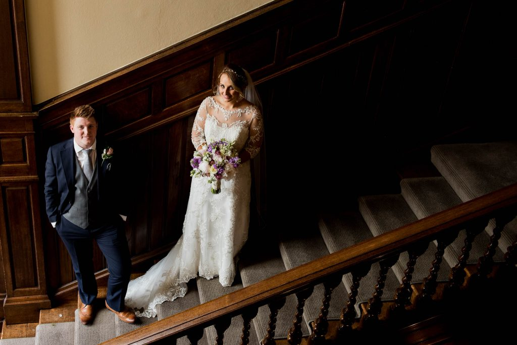 bride and groom posed on the grand staircase