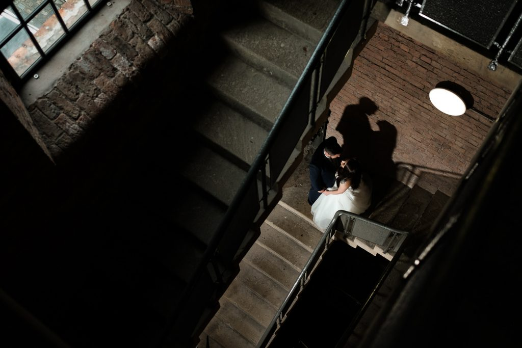 bride and groom posed on the stone staircase
