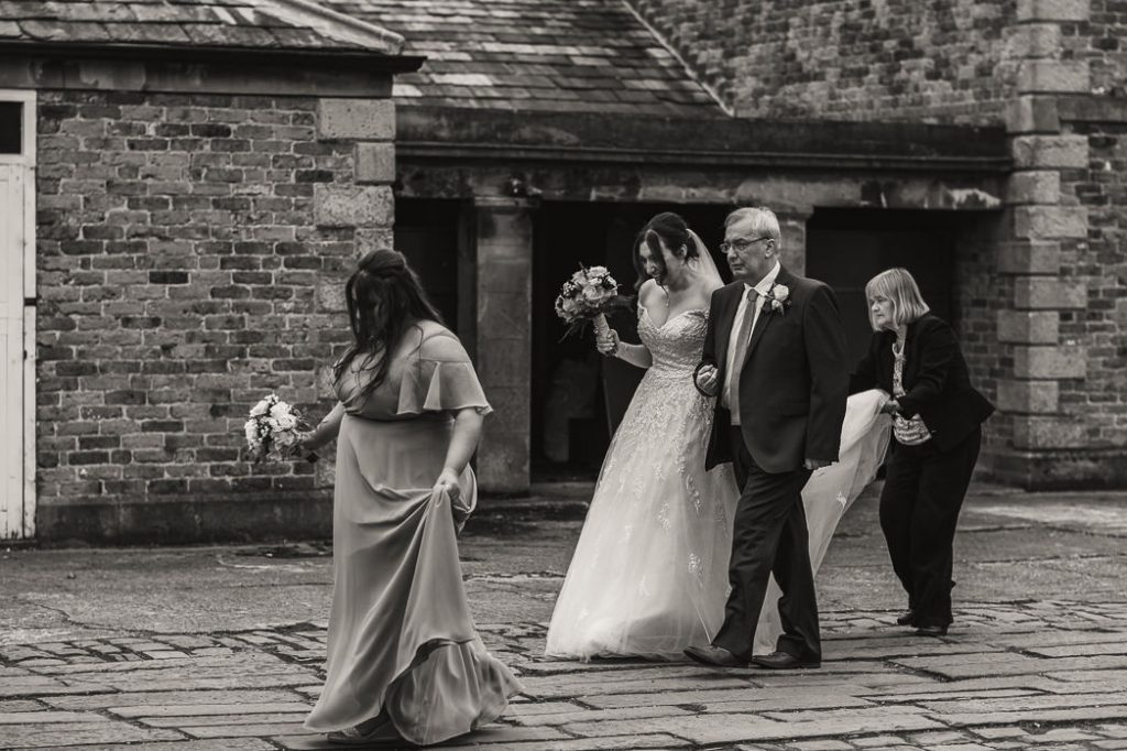 bride and her wedding party walking across the cobbles to get married