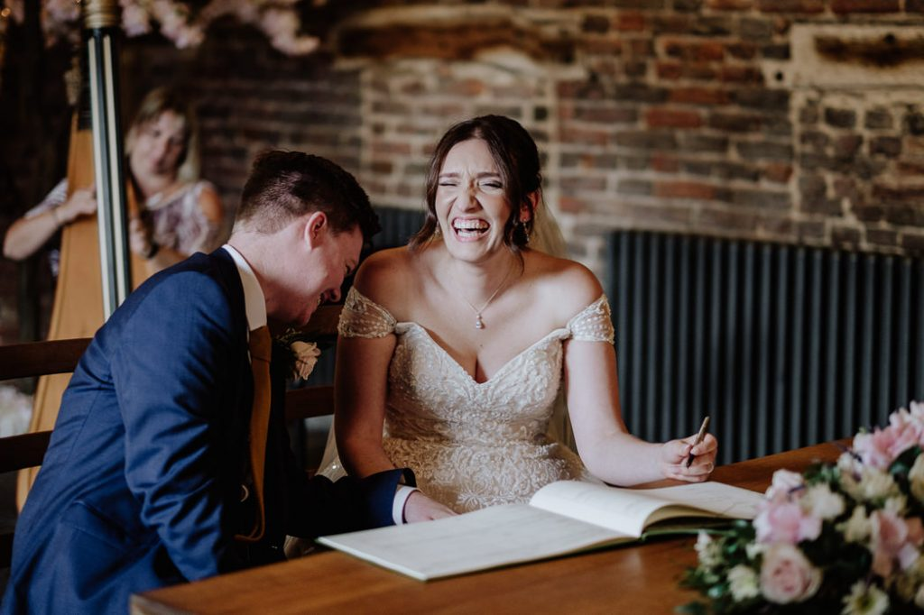 bride laughing during the signing of the register