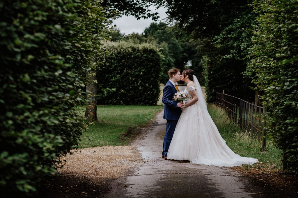 photograph the bride and groom kissing on the grounds of meols hall southport