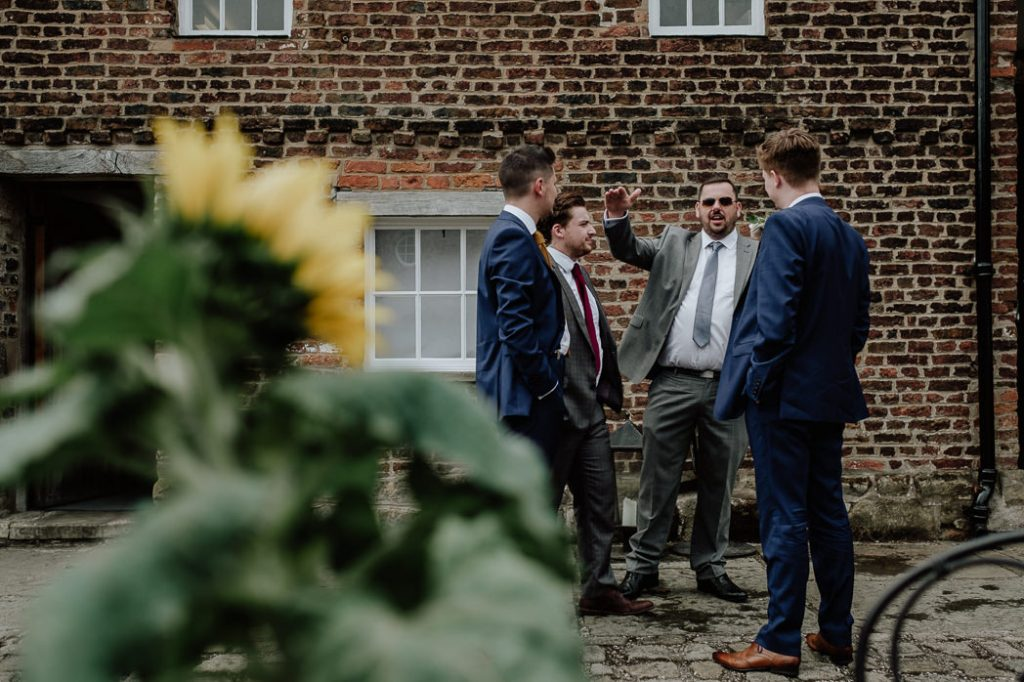 Groom and groomsmen joking around on the cobbles
