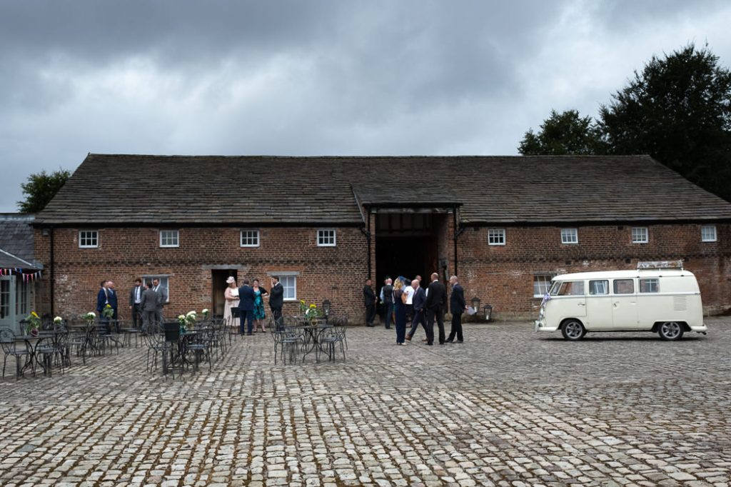 Wedding guest waiting on the cobbles at Meols Hall for the ceremony to begin