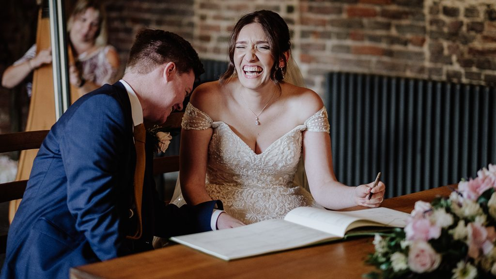southport wedding venue Meols Hall with a bride and groom laughing signing the register