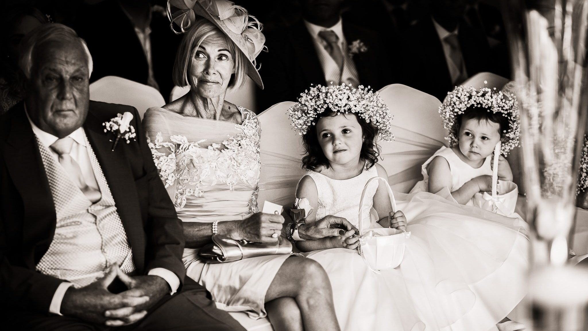 grandmother holding her grandchild's hand during the wedding ceremony